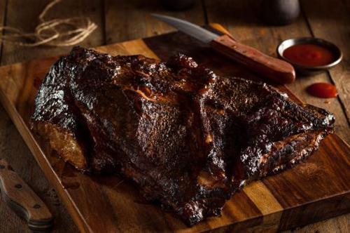BBQ Brisket on a wood cutting board with a steak knife