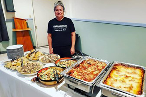 Patty behind catering table with lasagna, raviolis and much more
